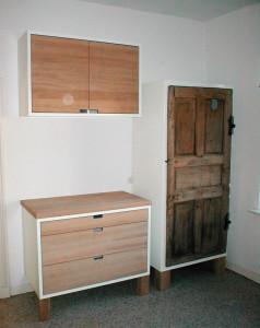 Alte Tür als Front für Küchenschrank. Dazu eine Ergänzung aus Massivholz. In Zusammenarbeit mit der Atelier Centrale.