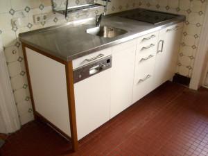 Edelstahl-Arbeitsplatte  und verdeckte Waschmaschine.