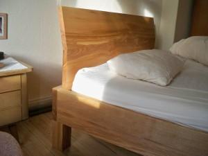 Bett aus Kernesche mit abgeknicktem Kopfteil.